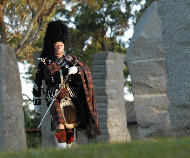 A piper walks through a stone circle